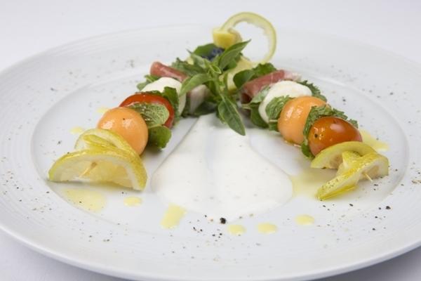 Espetinho de presunto de parma com melão, mozzarela de búfala e tomatinhos ao molho de iogurte e hortelã