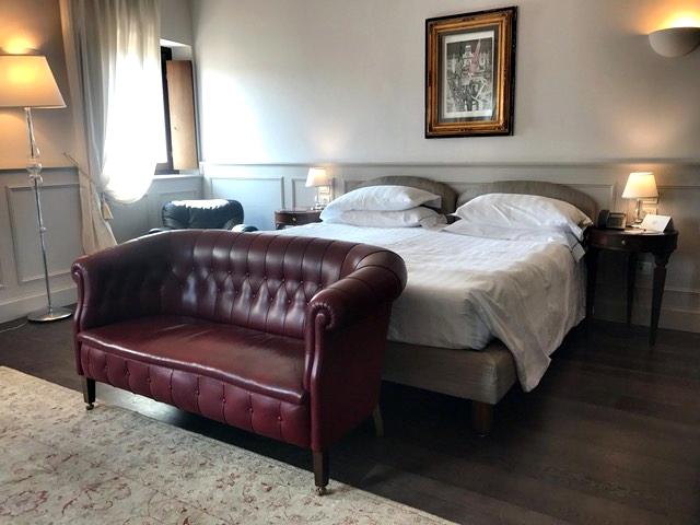 Quarto amplo com sofá, poltrona e cabeceira