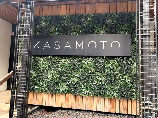 fachada de um restaurante com letreiro e plantas