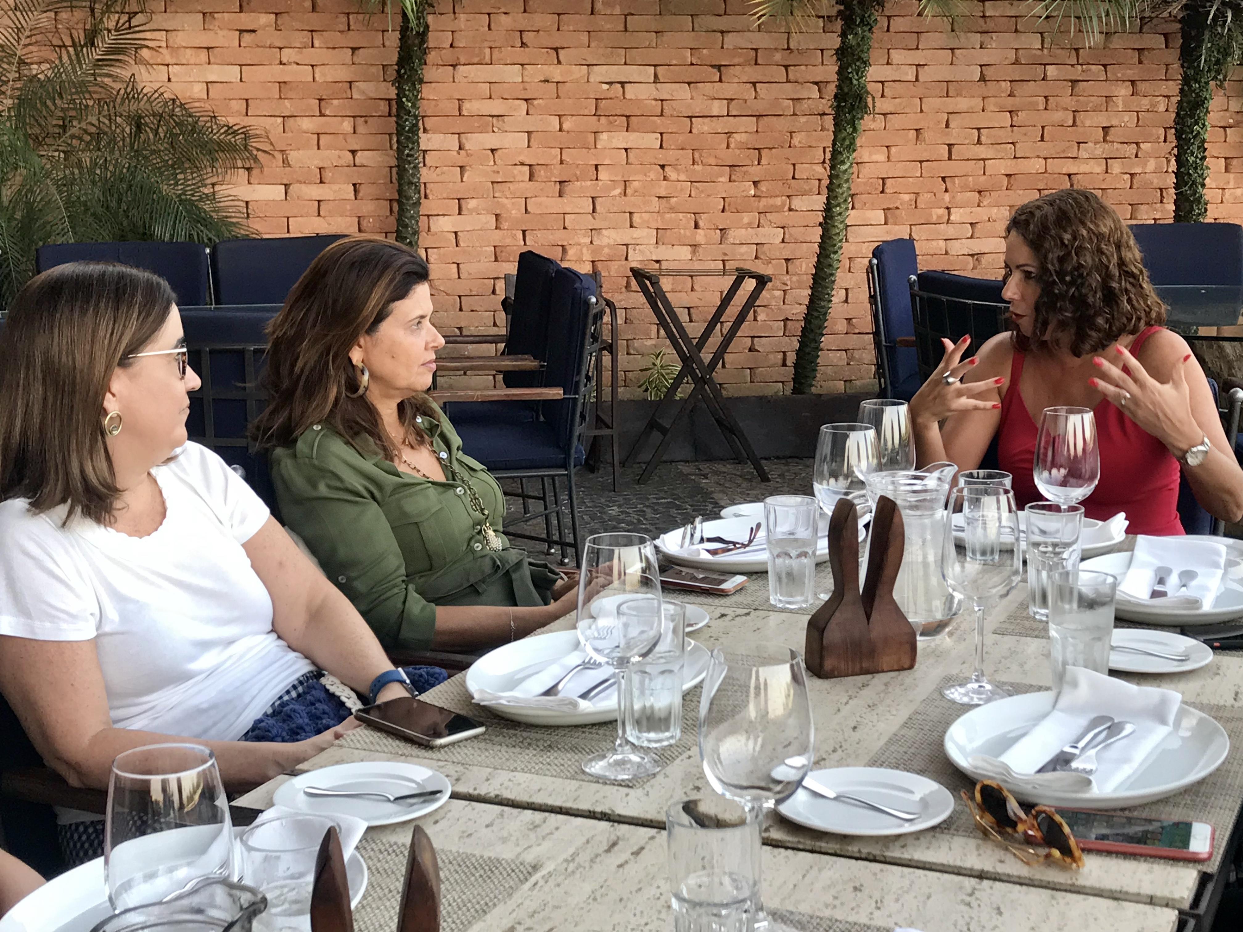 três mulheres sentadas na mesa