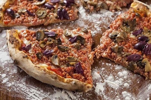 Pizza artesanal toscana com molho San Marzano, muçarela, calabresa artesanal moída, cogumelos paris, azeitonas pretas fatiadas e orégano.