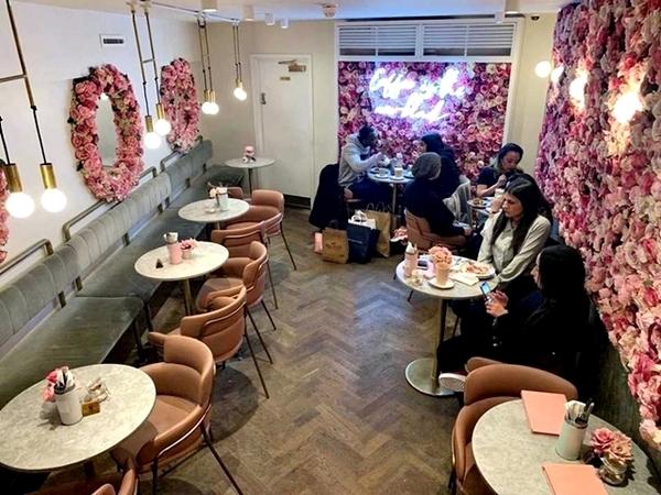 ambiente com mesas e cadeiras, flores rosas